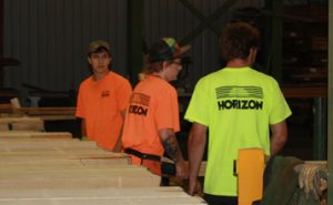 Staff members regrading lumber
